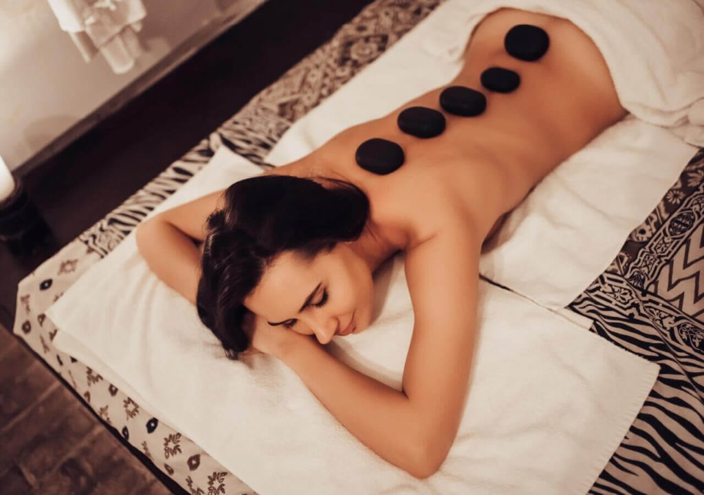 Woman receives a hot stone massage at spa